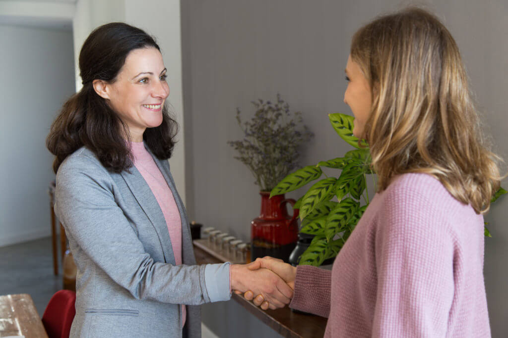 Two smiling women standing and shaking hands. Attractive woman wearing casual clothes and sealing deal with client in office. Agreement concept.