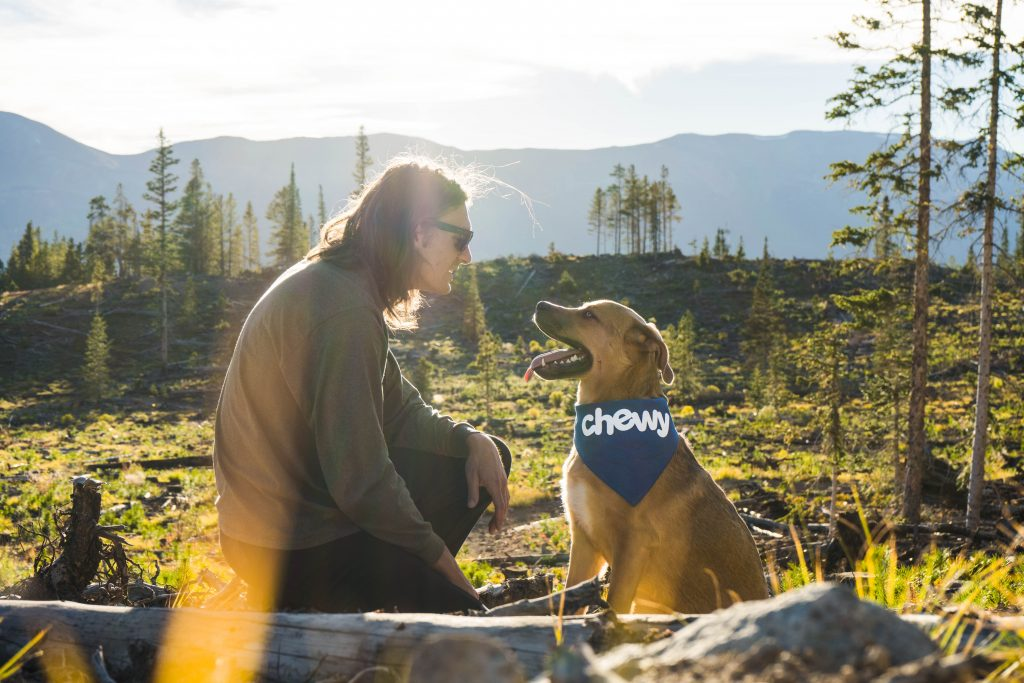 """Happy dog and happy owner. Dog is wearing bandana which says """"chewy""""."""